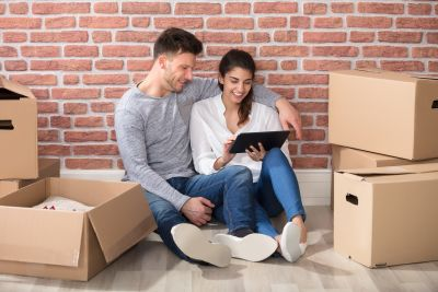 couple sitting between boxes lewis apartment homes moving