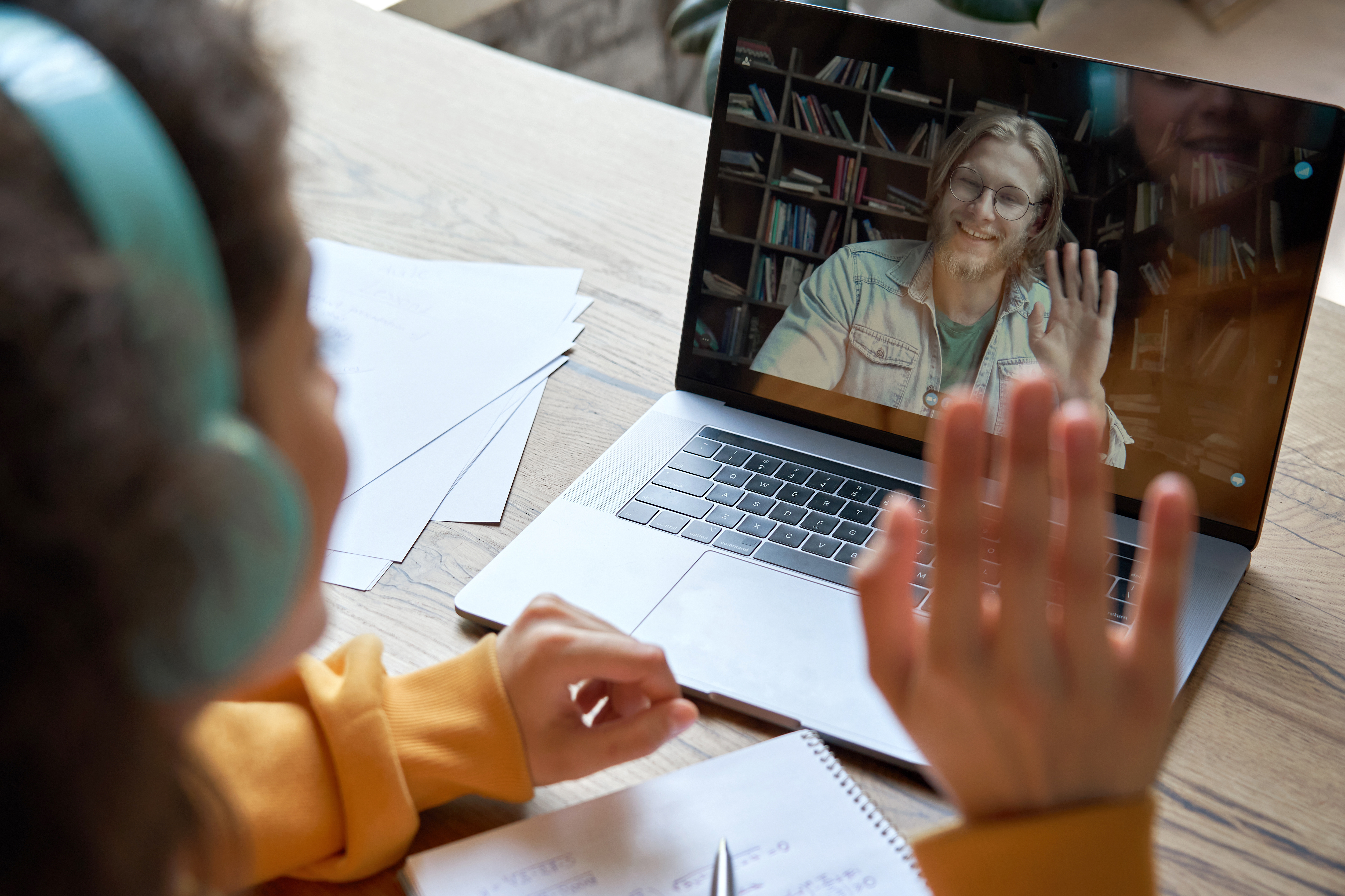 Hispanic teen girl school college student distance learning waving hand studying with online teacher on laptop screen. Elearning zoom video call, videoconference class with tutor. Over shoulder view