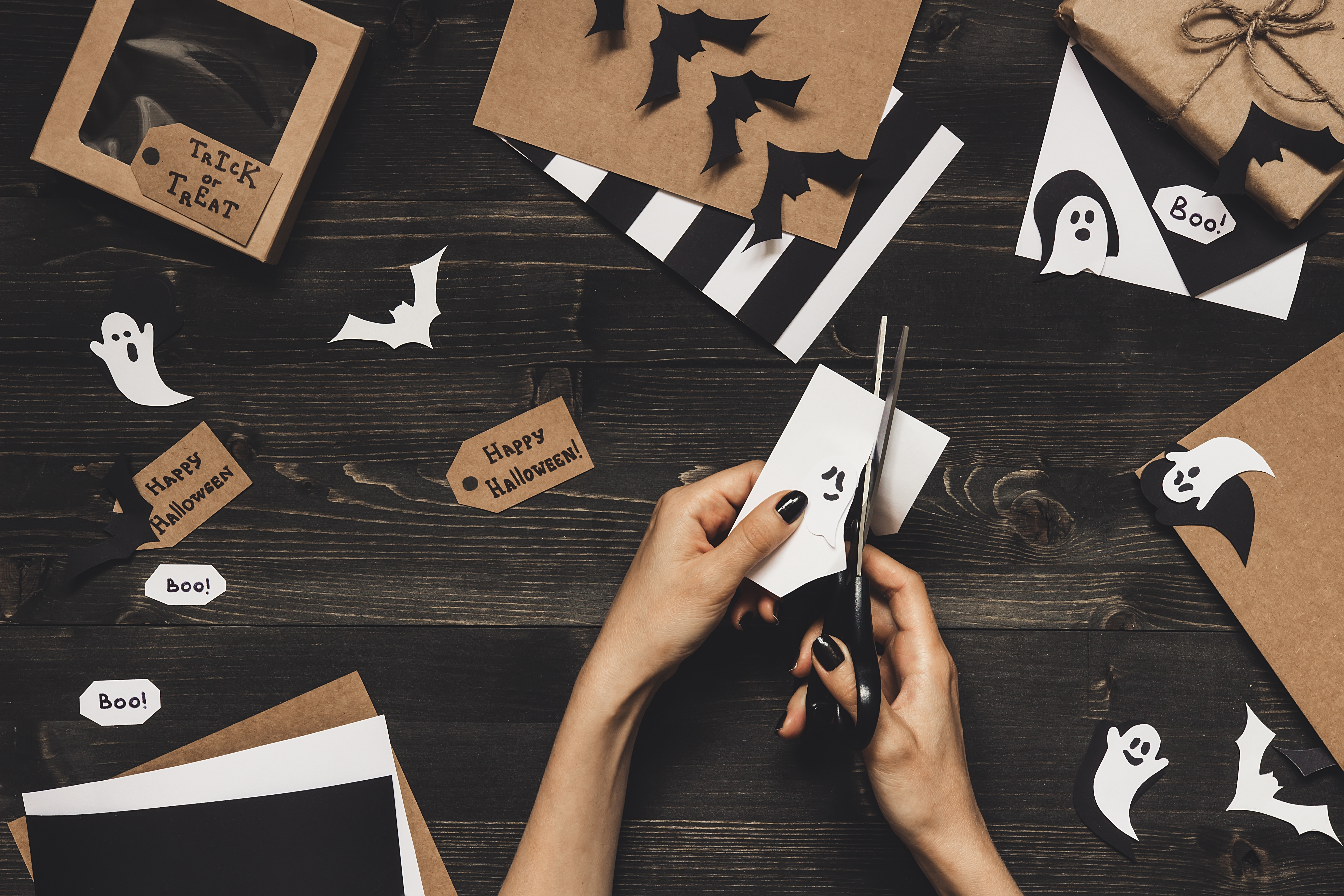 Halloween preparation. Hands making halloween cards and decoration using craft paper.
