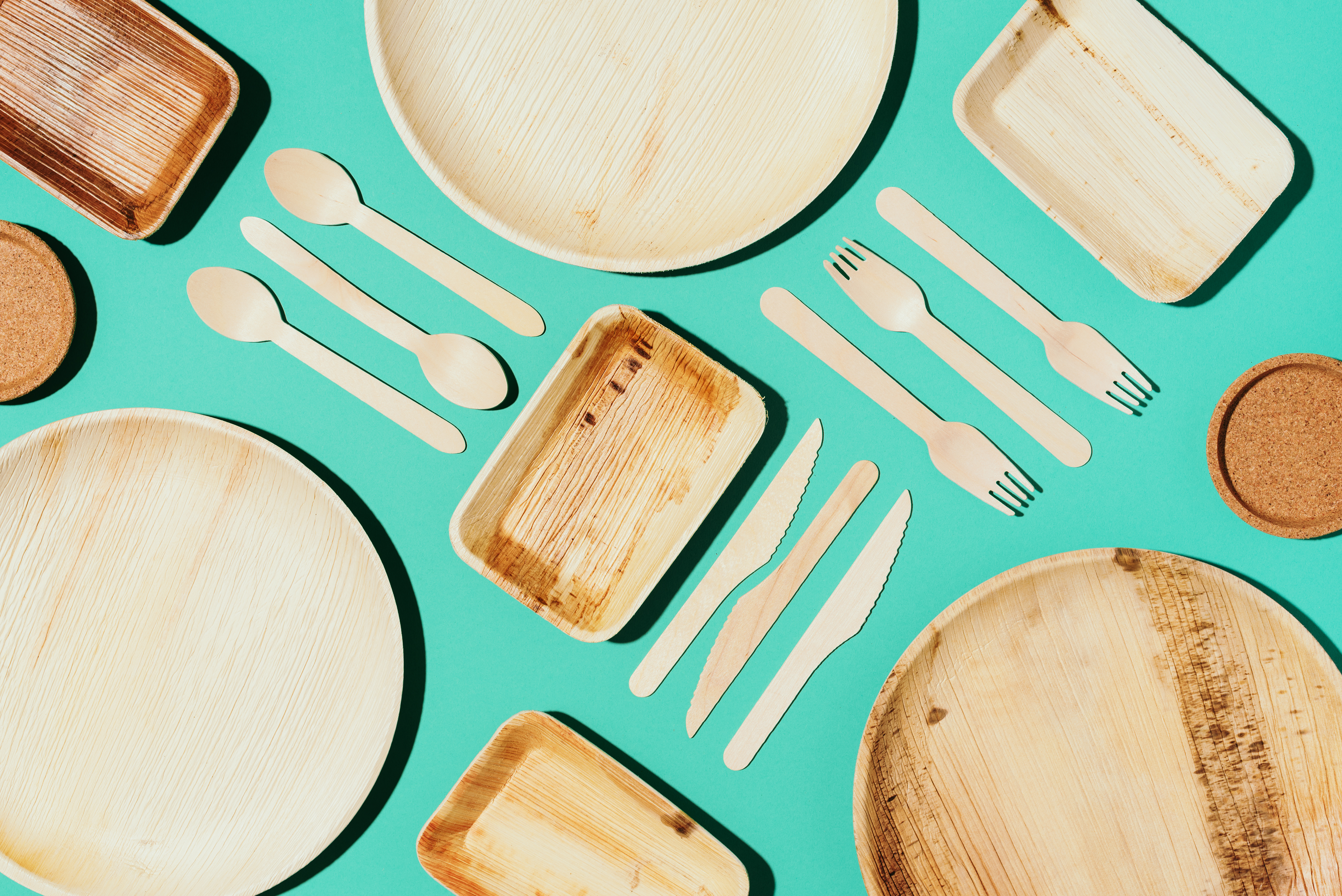 Bamboo plates, wooden spoon, fork, knife, craft paper cups on blue background. Disposable tableware from natural materials. Sustainable lifestyle concept. Eco-friendly disposable utensils.